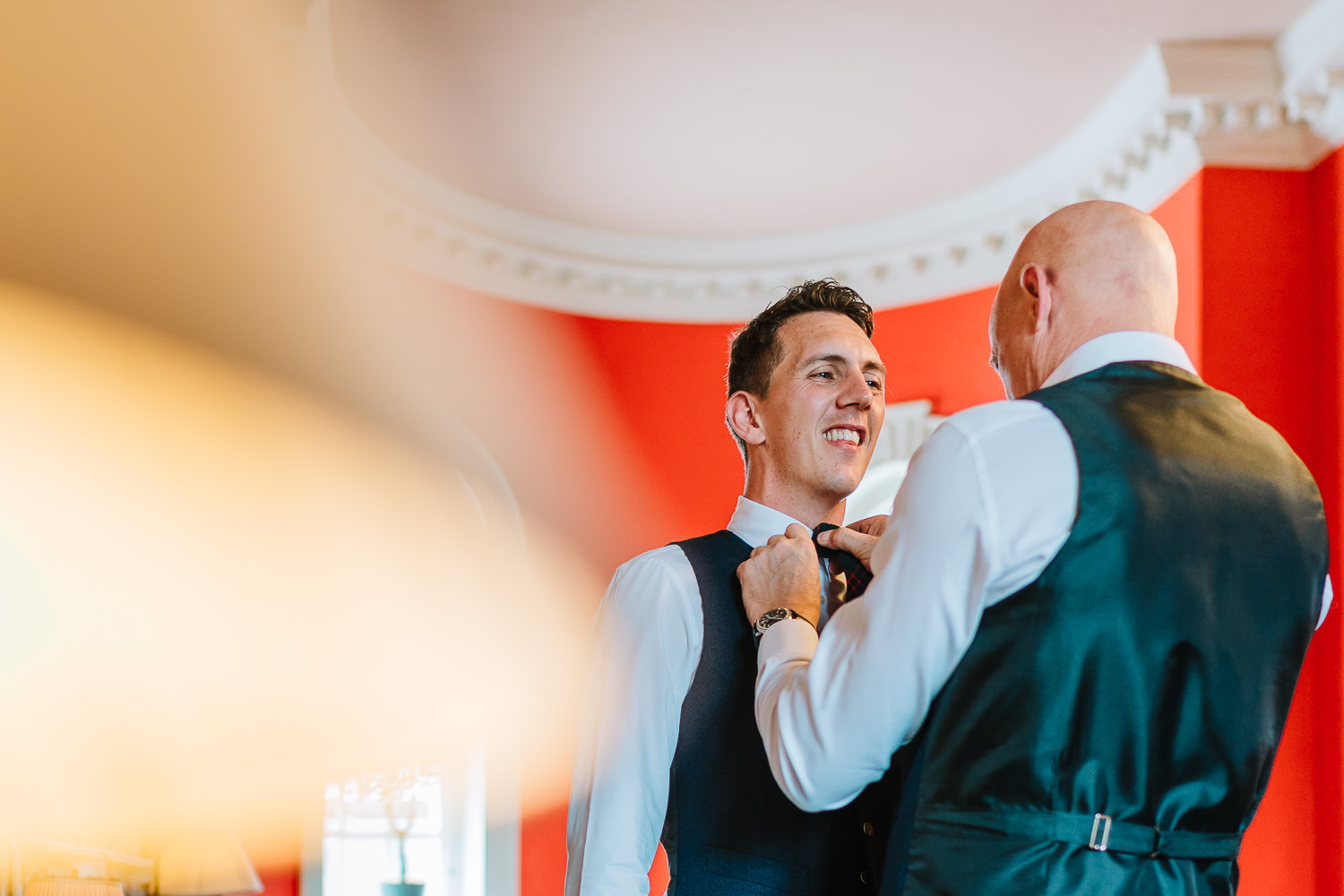 The groom having his tie done by his father.