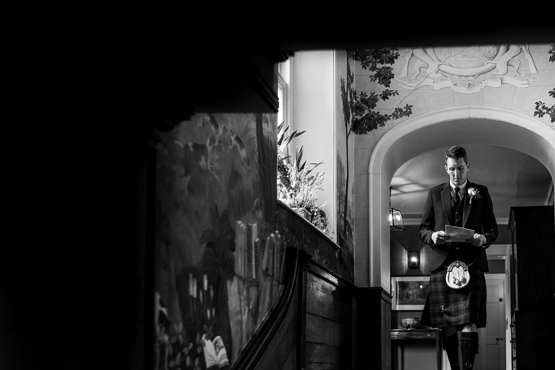 The groom walking through Iscoyd Park reading his speech