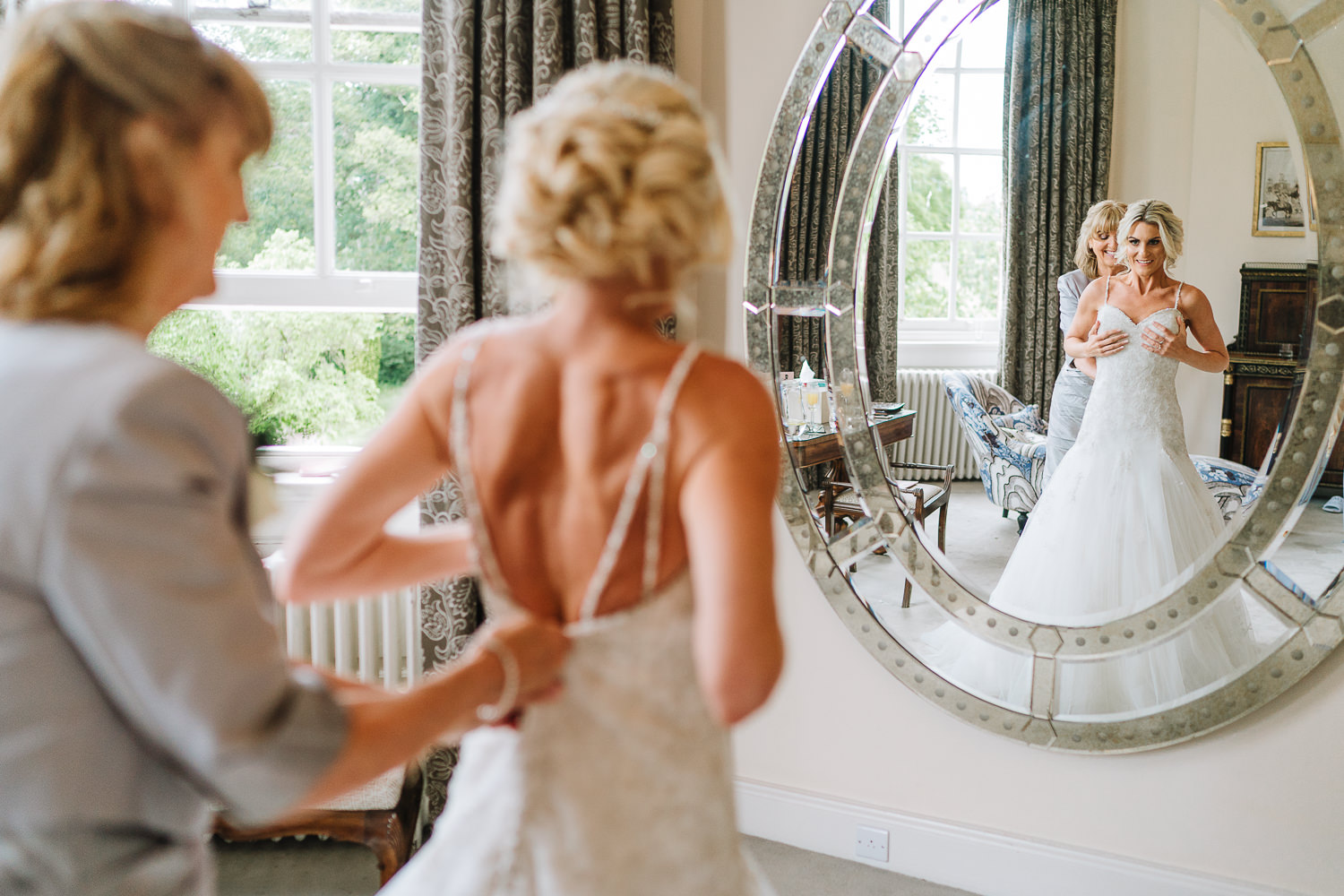 Bride putting her dress on with her mum's help