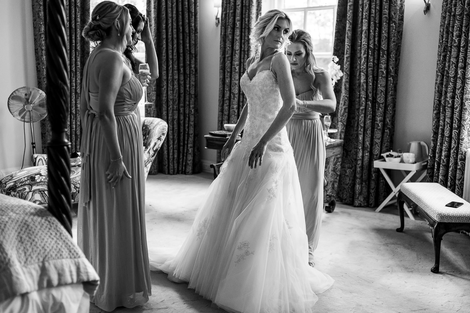 Bride putting on her dress with her bridesmaids