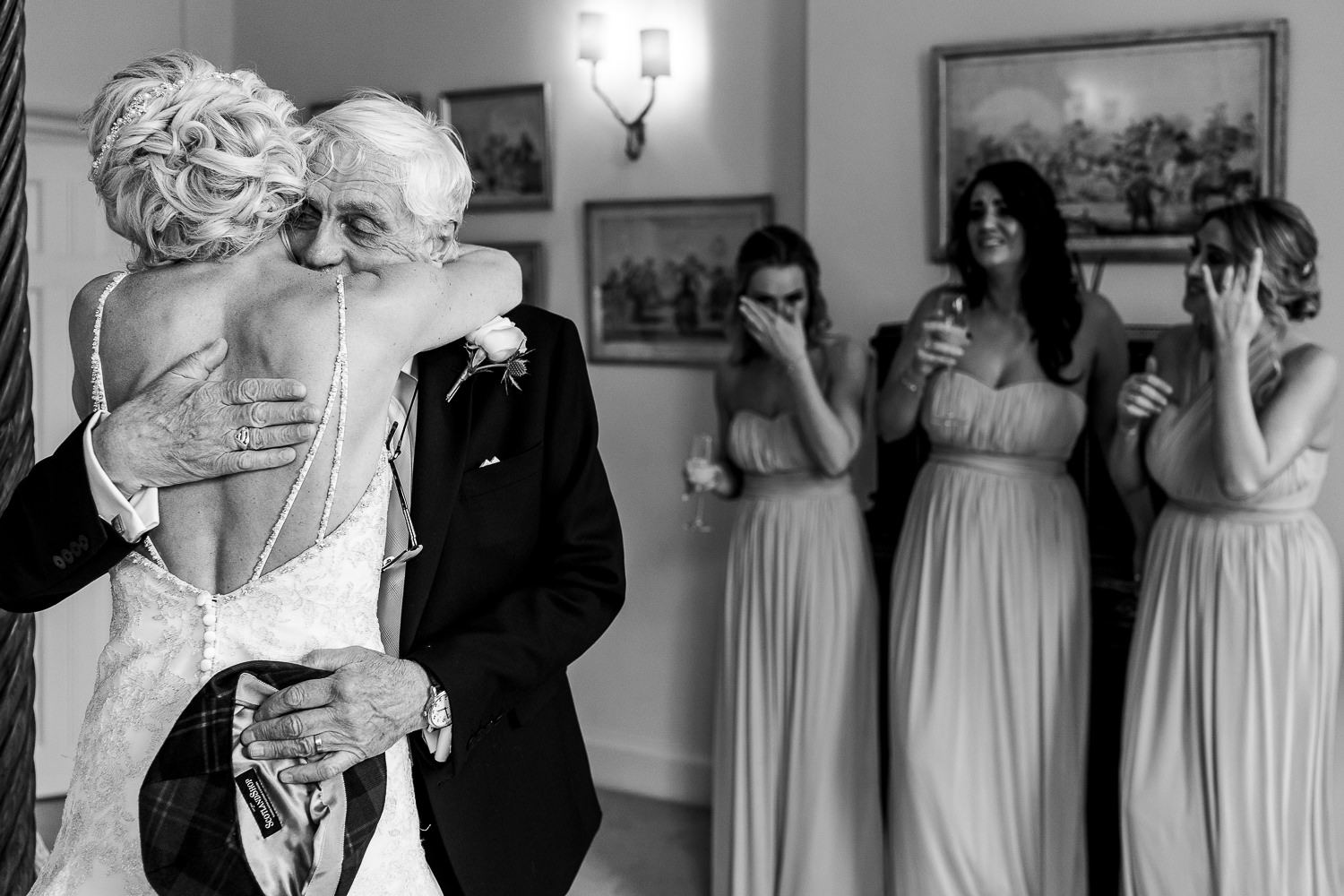Bride hugging her dad with her bridesmaids crying in the background.