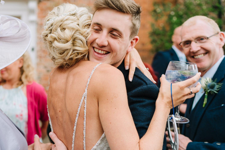 Bride hugging a groomsman