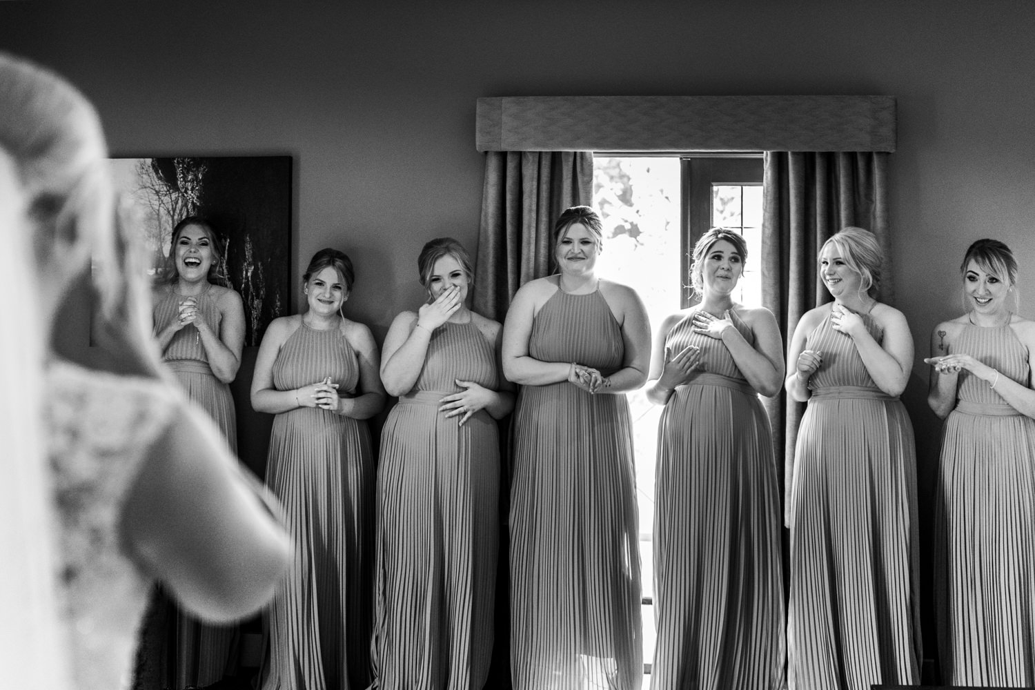 Bridesmaids crying and laughing at seeing the dress