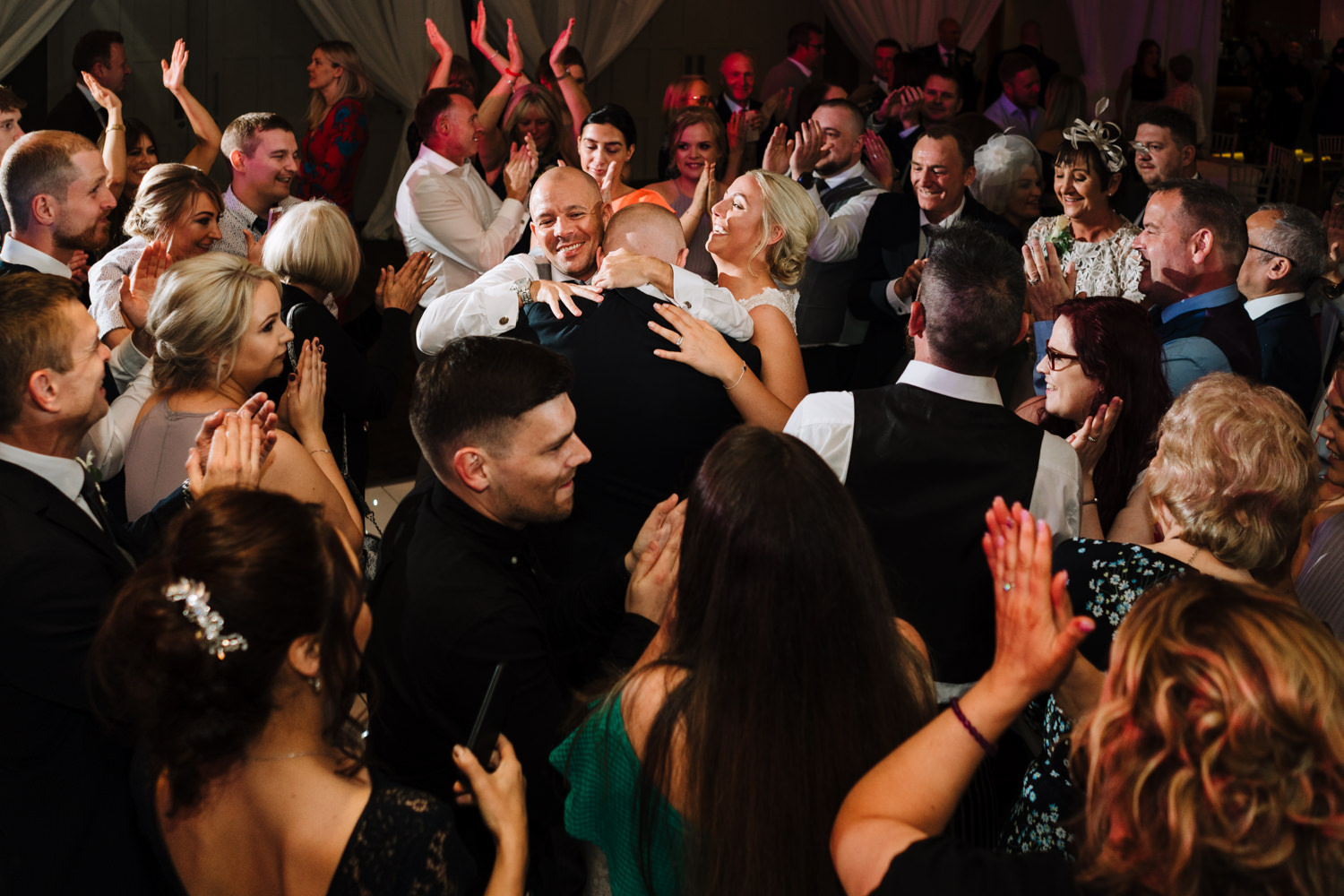 Packed dance floor at the Mere with bride and groom in middle