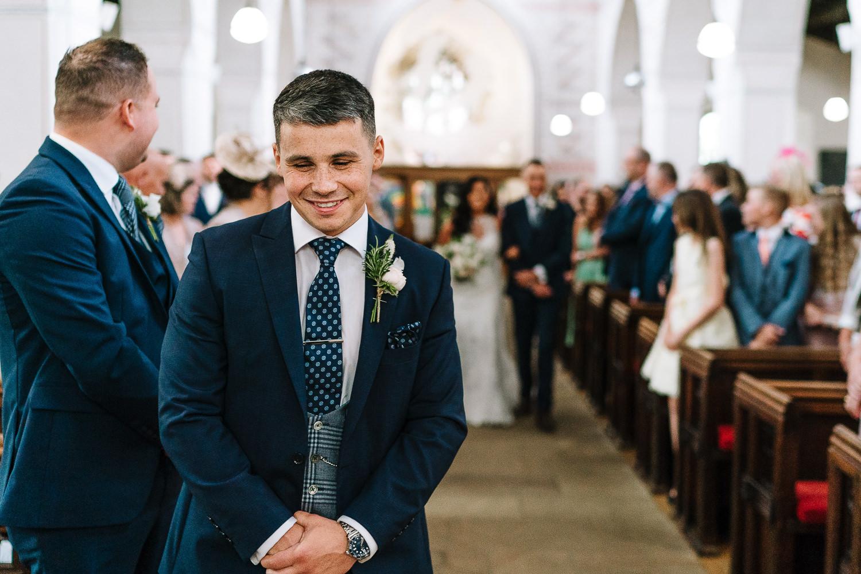 Groom smiling as bride is walking down the aisle