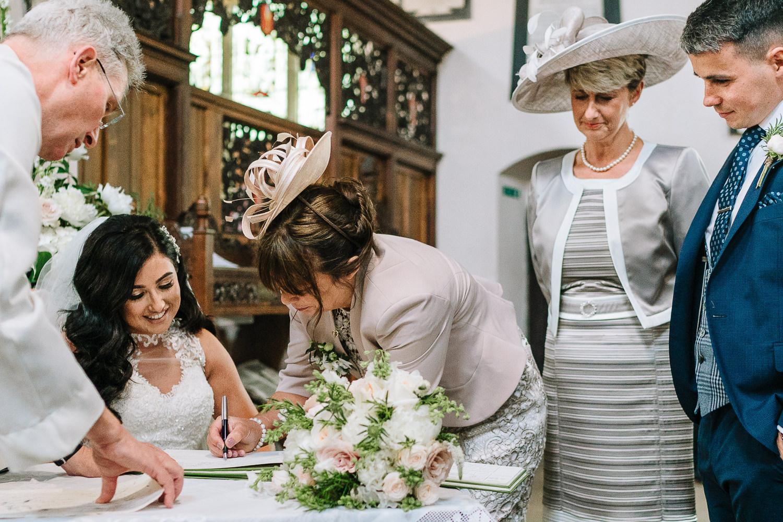 Grooms mum signing the register