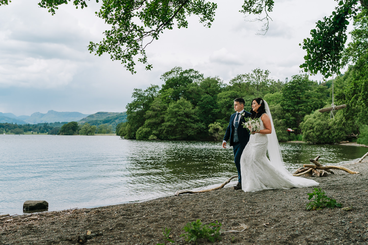 Photo of the bride and groom walking by the lake