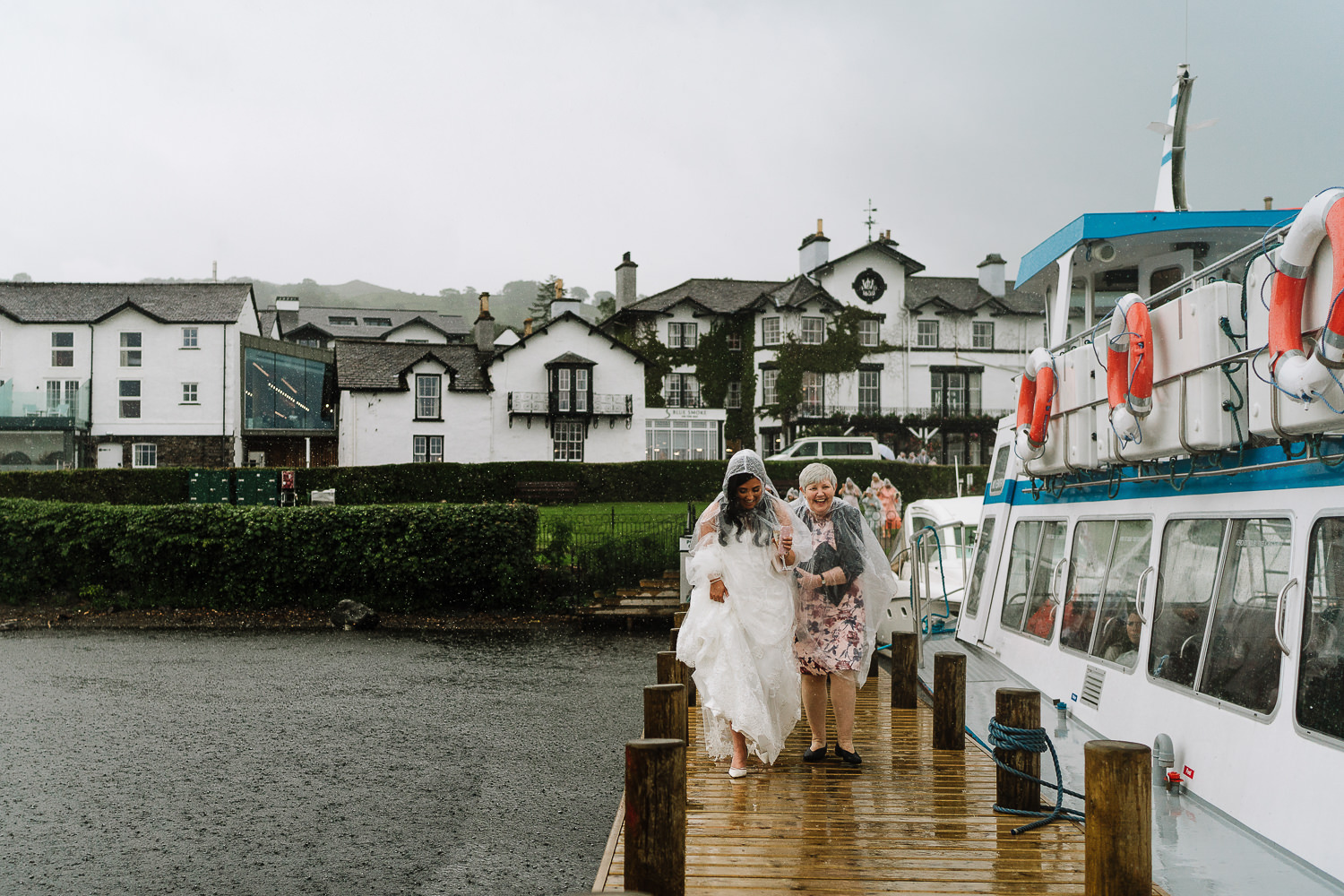 Guests getting on boat in rain on the jetty at Low Wood Bay