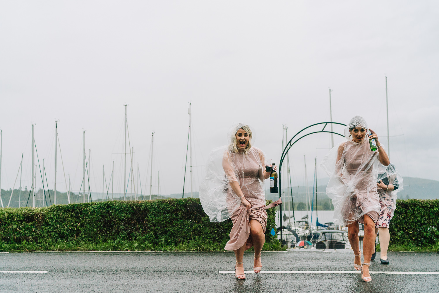 Bridesmaids walking across the road from the boat in the rain
