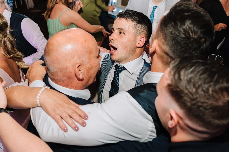 groom hugging his dad on dancefloor
