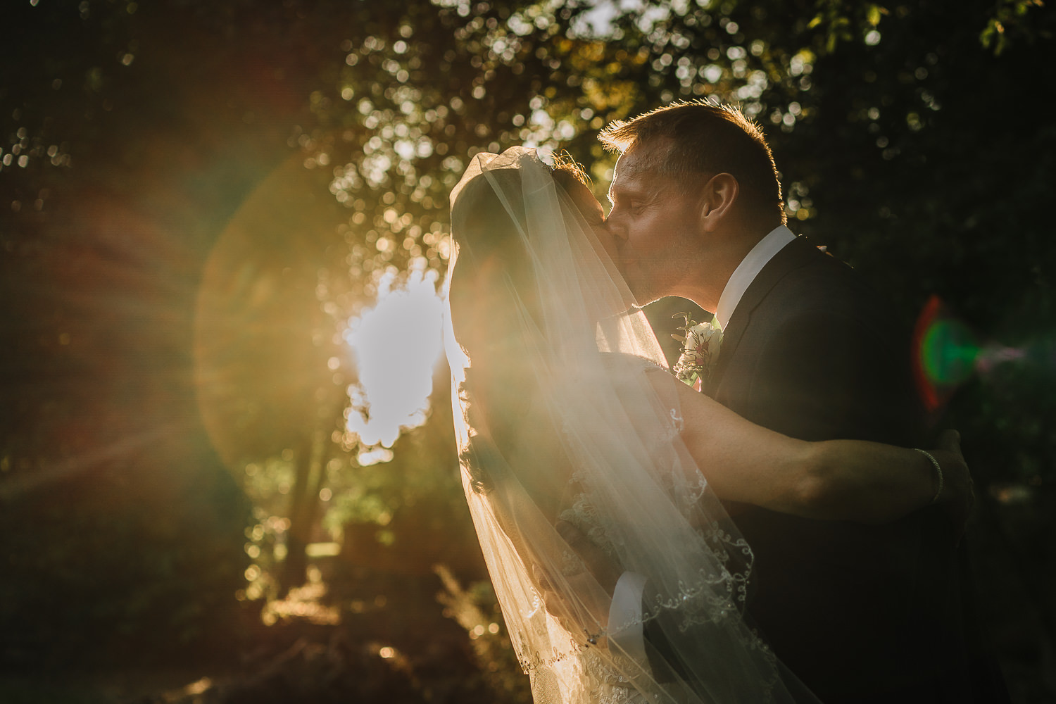Bride and groom kissing in the sun