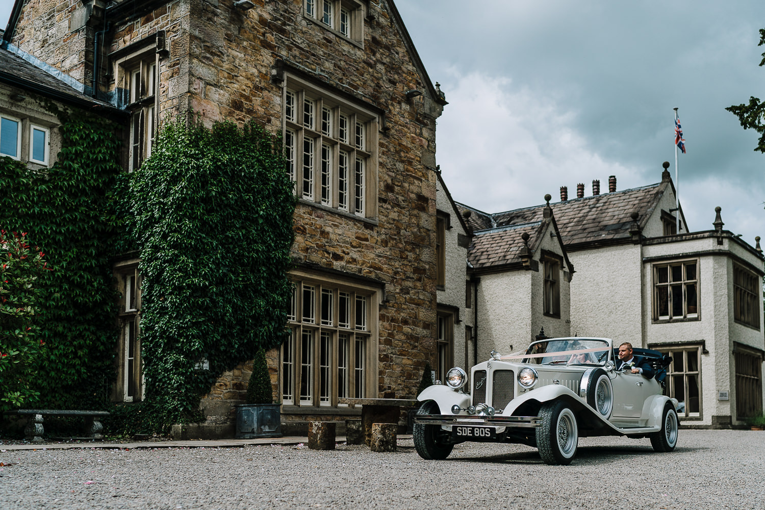 bride and groom arriving in the wedding car outside Mitton hall