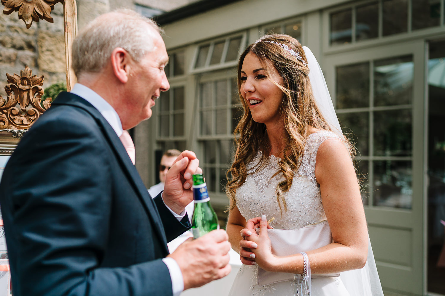 bride laughing with her dad outside Mitton Hall