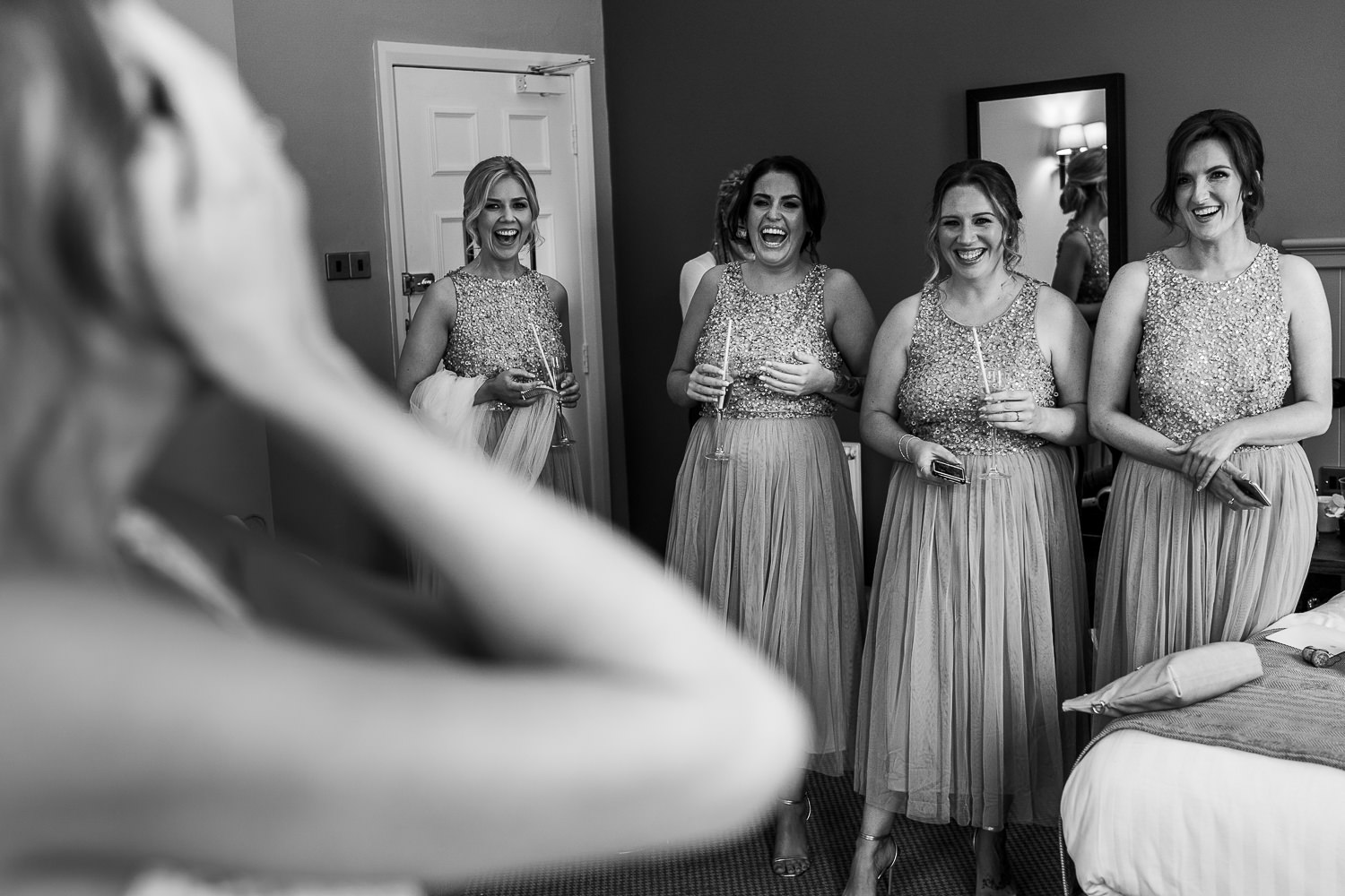 Bride crying with her bridesmaids laughing in the background