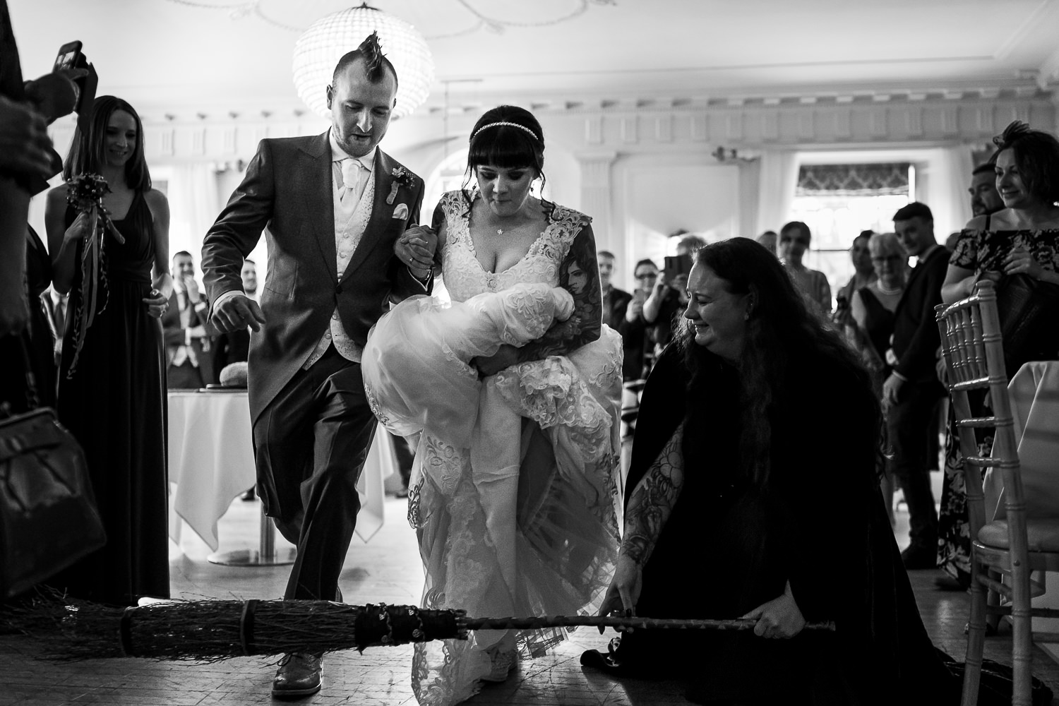 bride and groom jumping over a broom