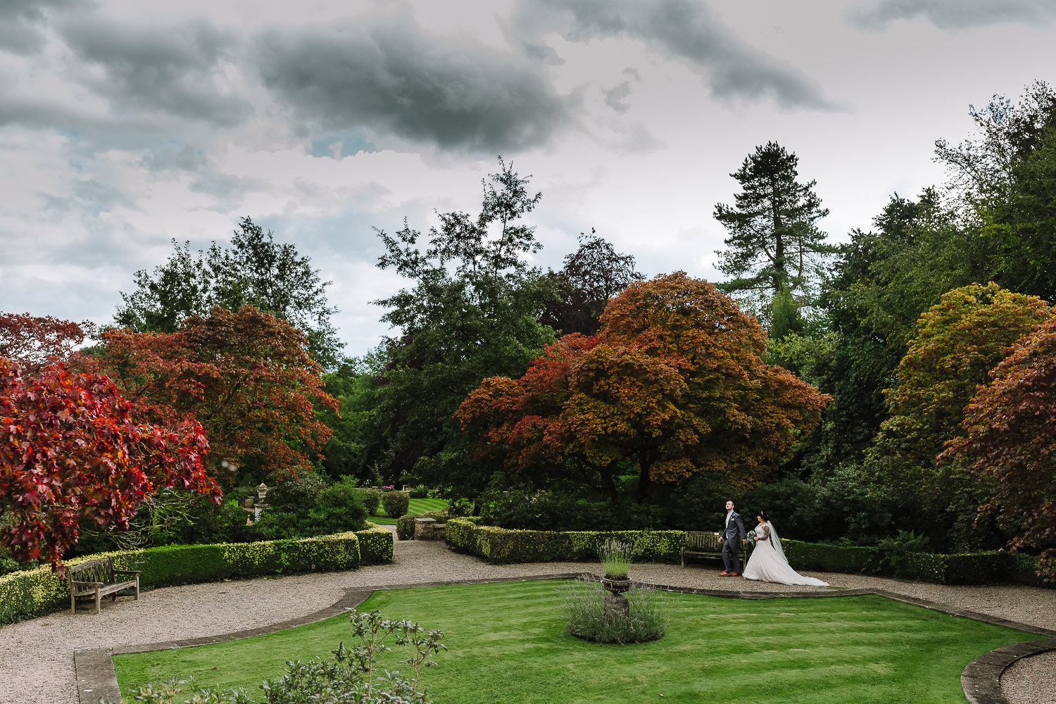 bride and groom walking in the gardens at Eaves Hall