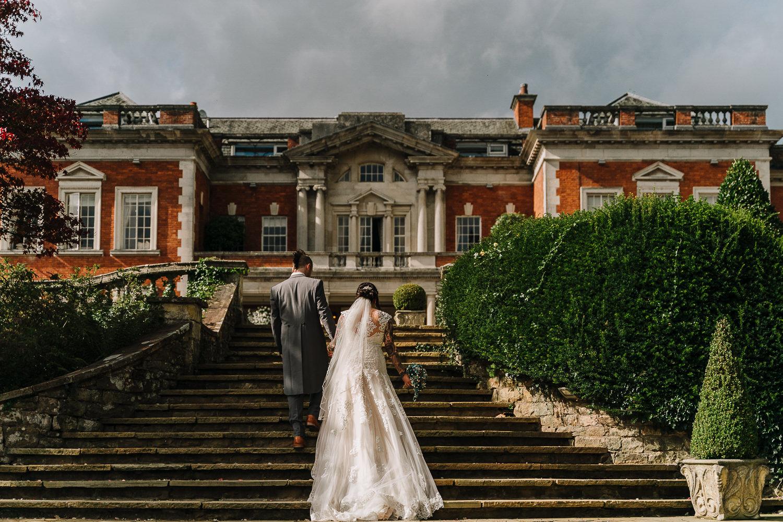 bride and groom walking in Eaves Hall