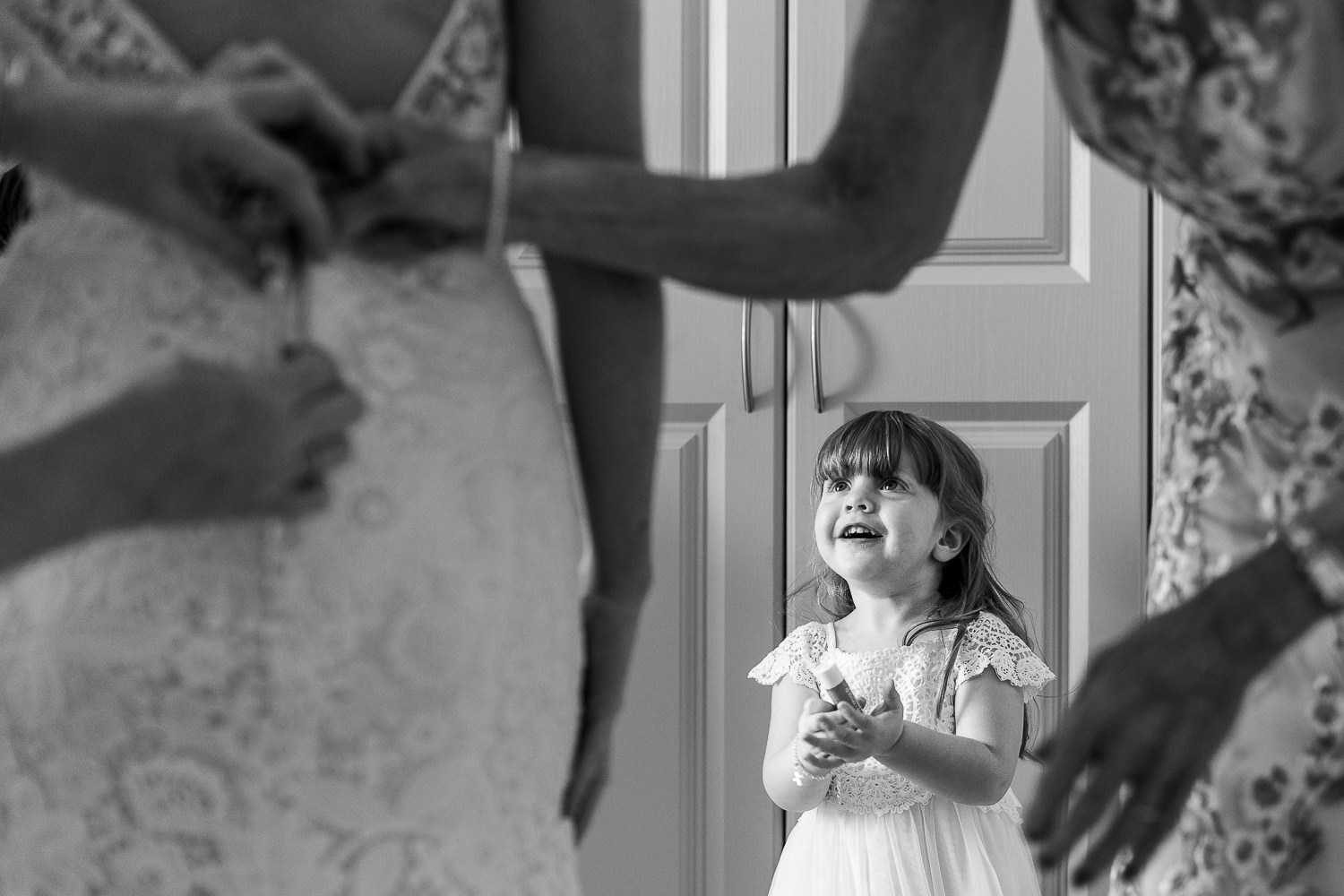 flower girl looking at bride in dress