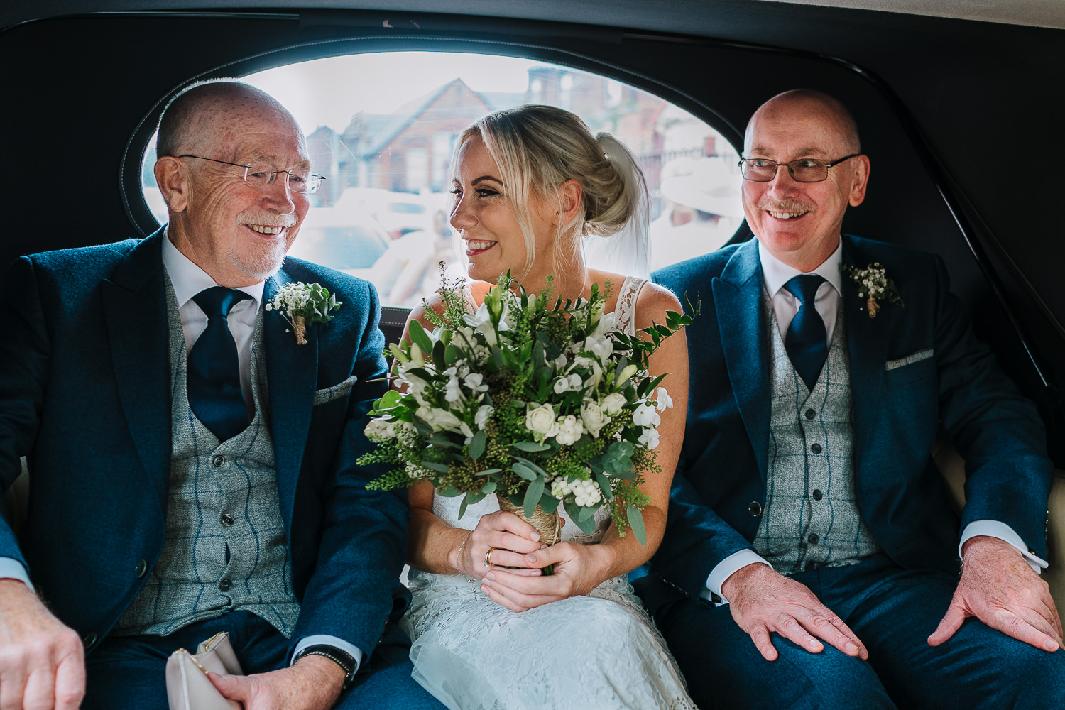 bride in car with dad and step dad