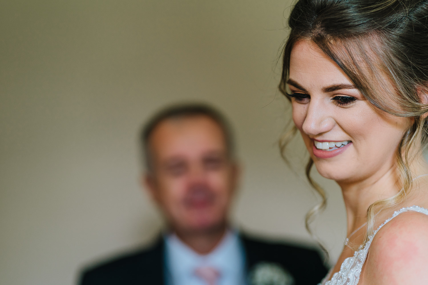 bride smiling with her dad in background