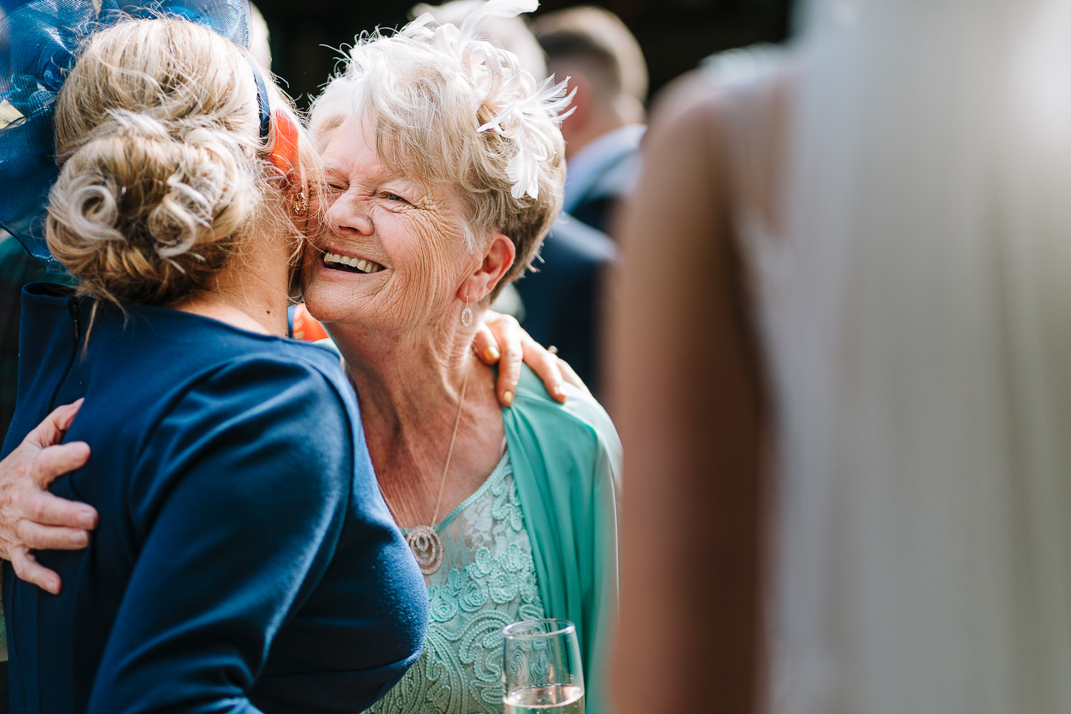 Brides gran laughing and hugging during drinks reception
