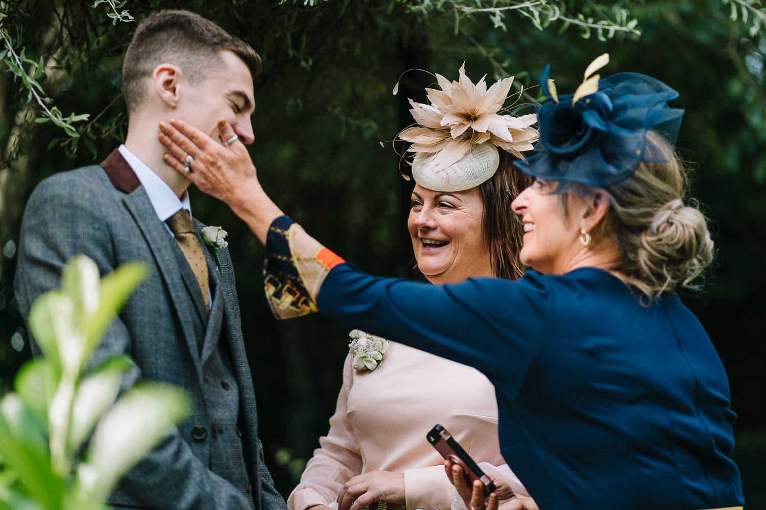 mother of bride and her brother laughing with a guest