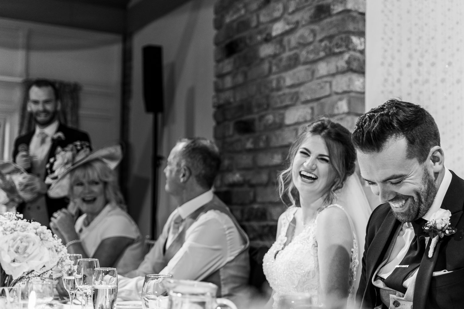 bride laughing with groom during speeches