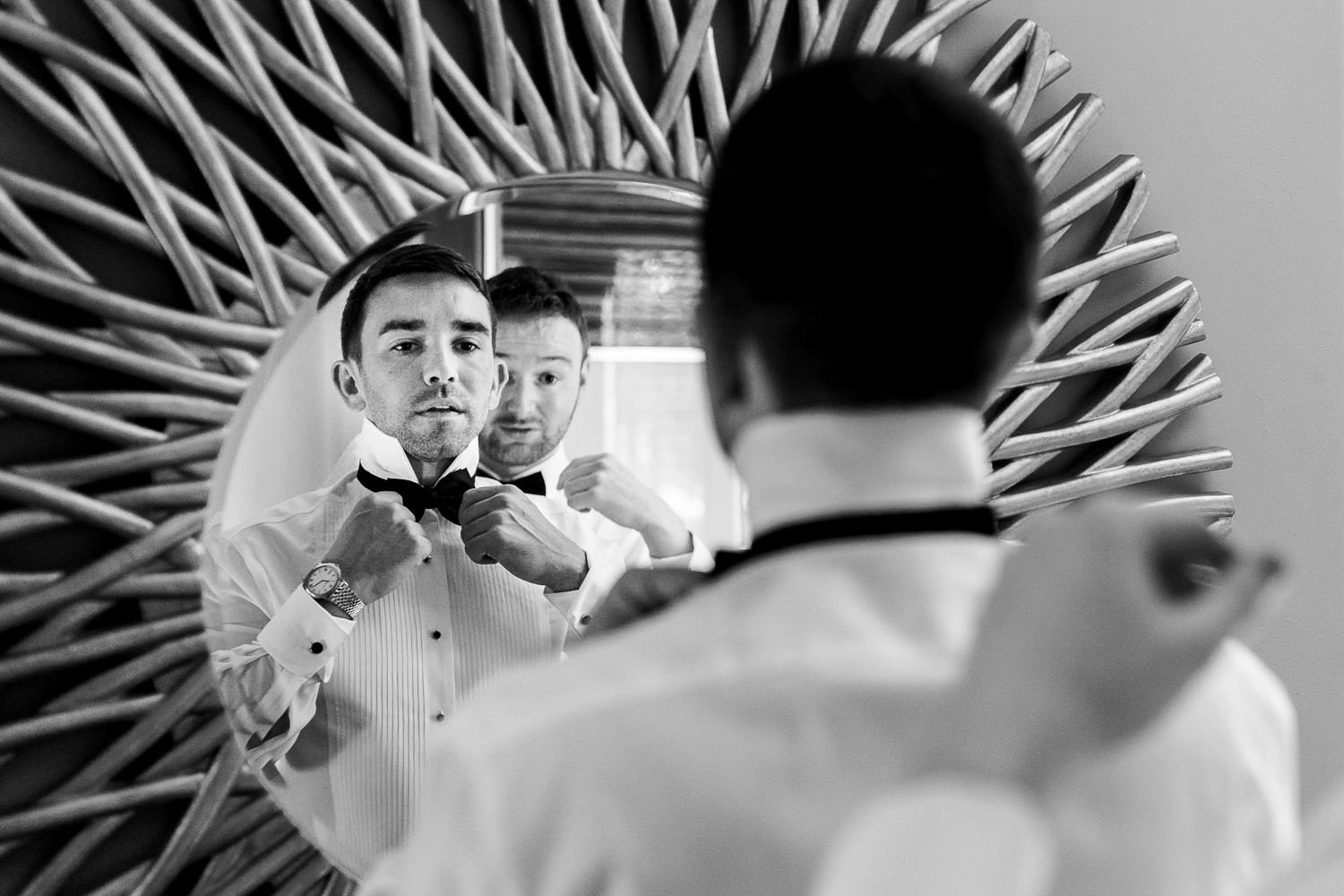 Groomsmen getting ready in the mirror at Colshaw Hall
