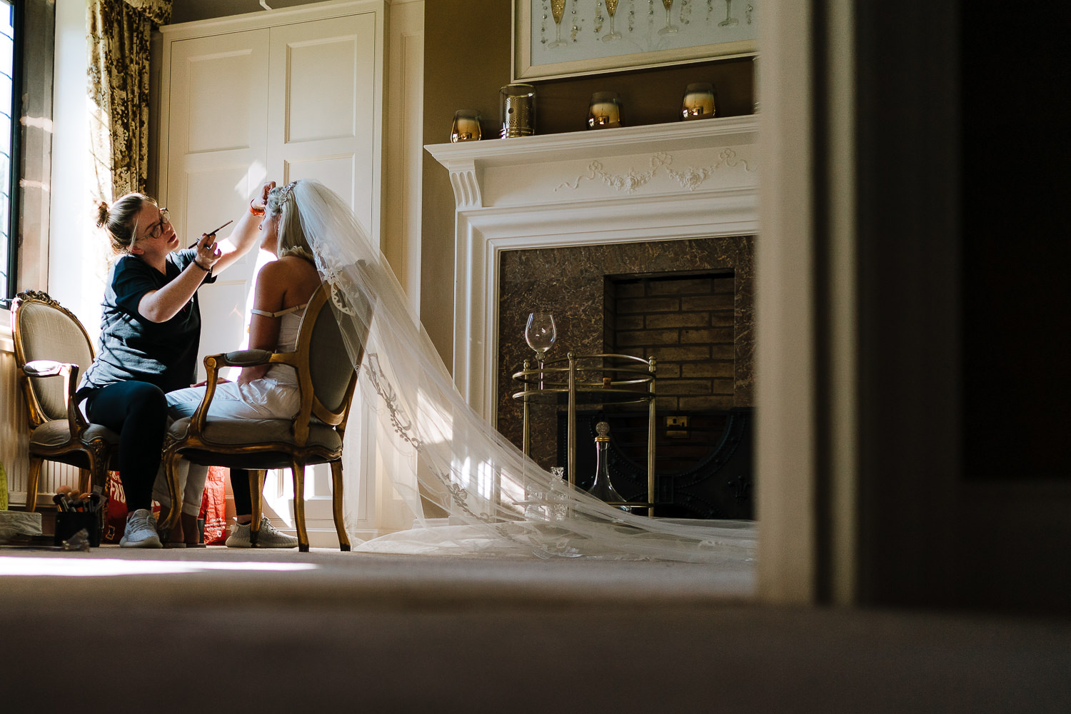Bride having her make up done sitting in her veil at Colshaw Hall's bridal Suite