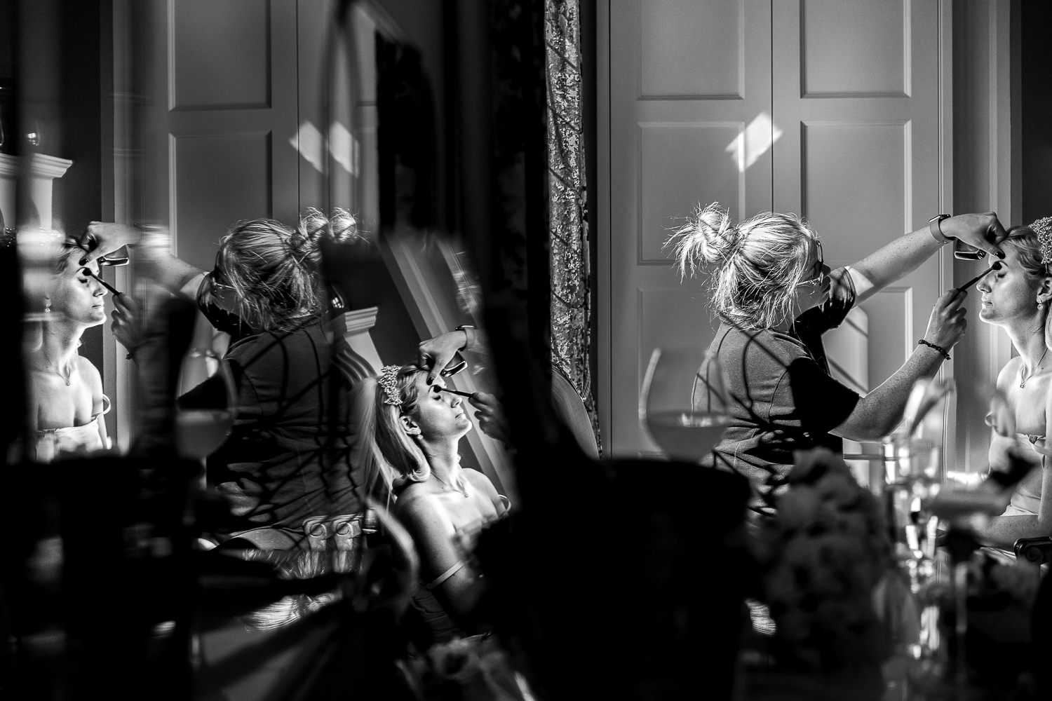 Bride having her make up done in the mirror of Colshaw Hall