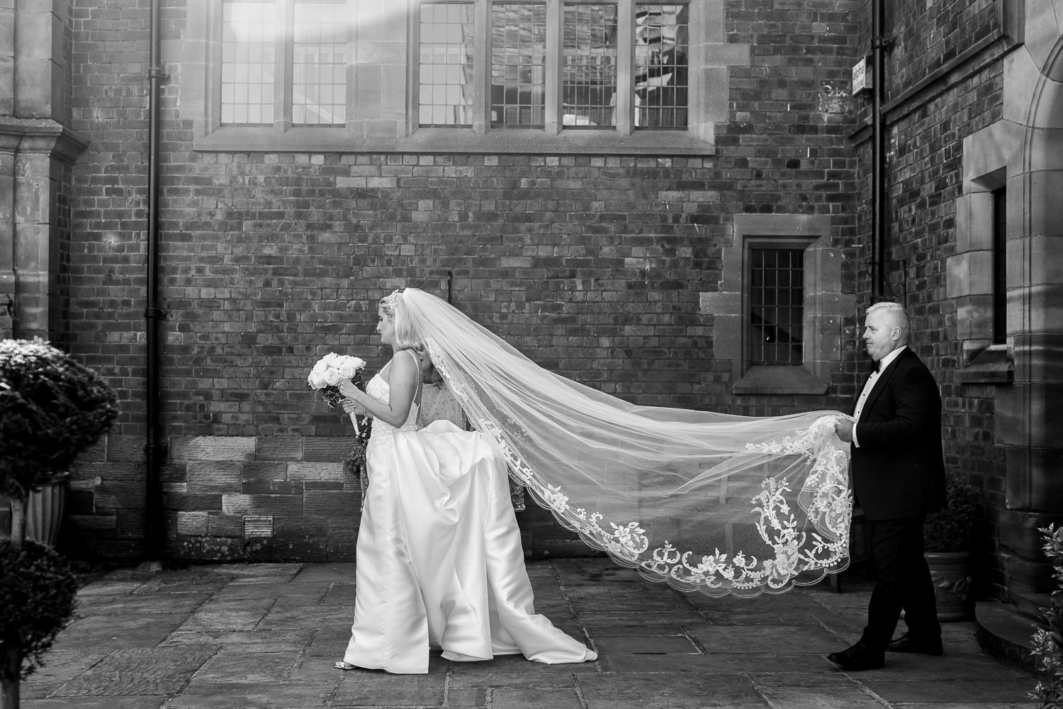Bride walking outside with her dad carrying her veil