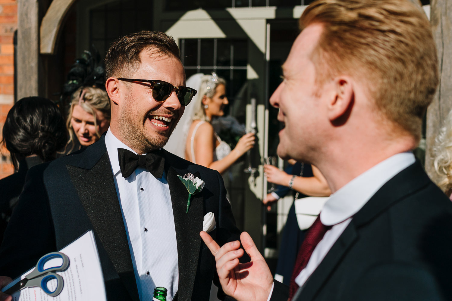 Groom laughing with a guest