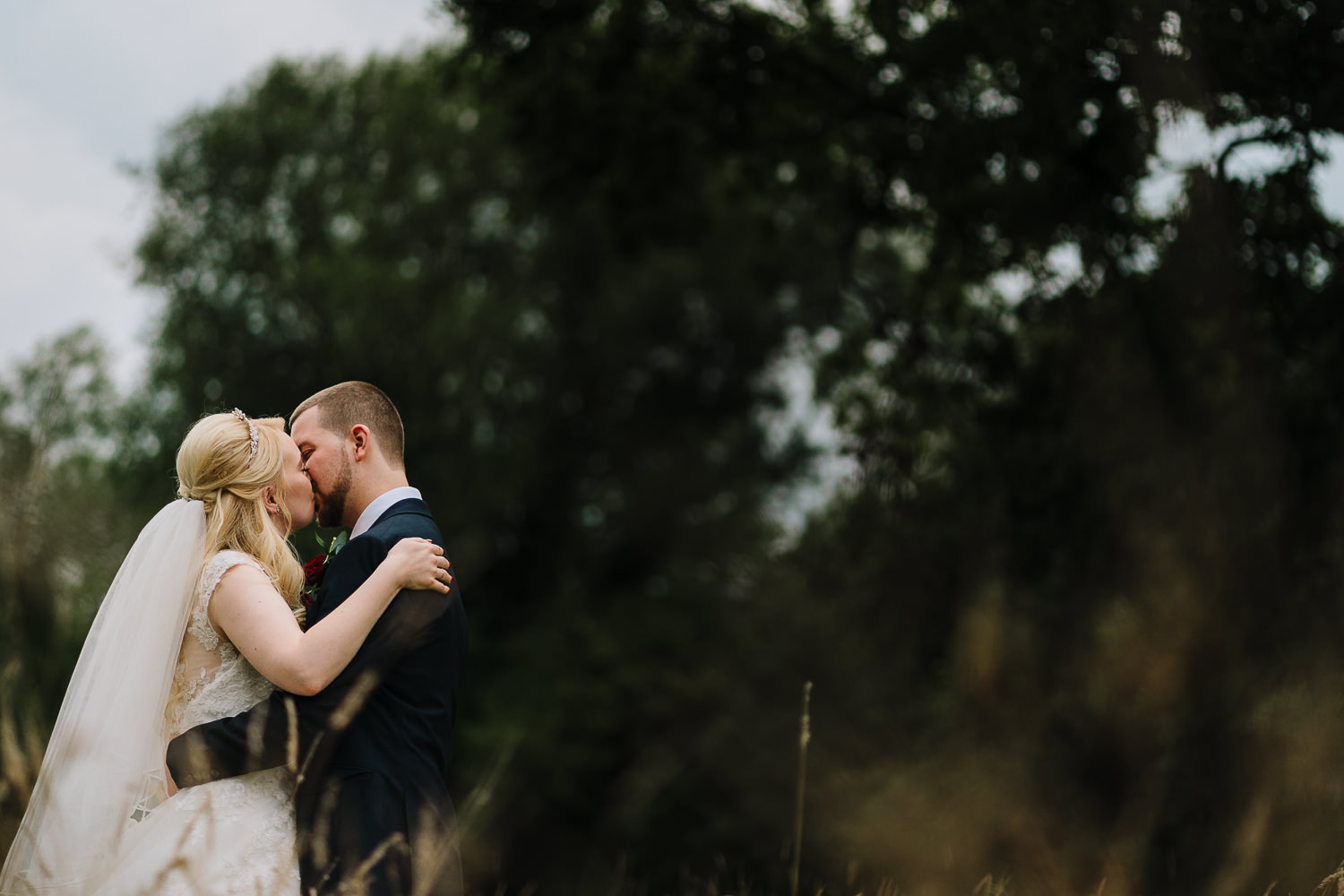 bride and groom kissing in the fields
