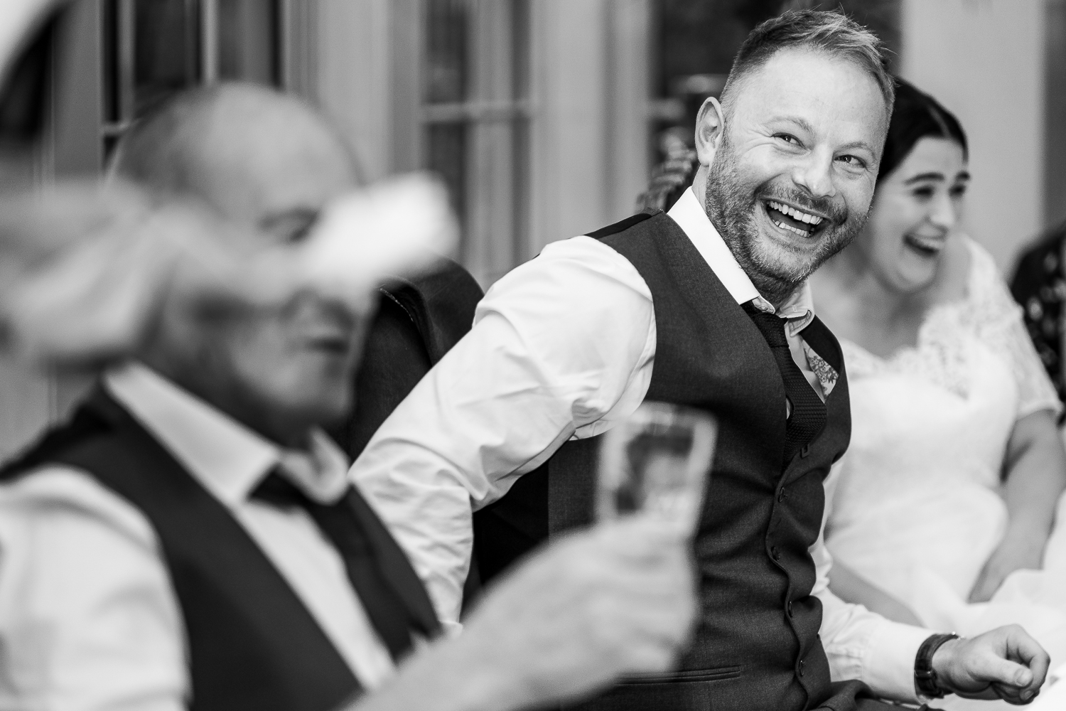 Groom laughing at best man speech