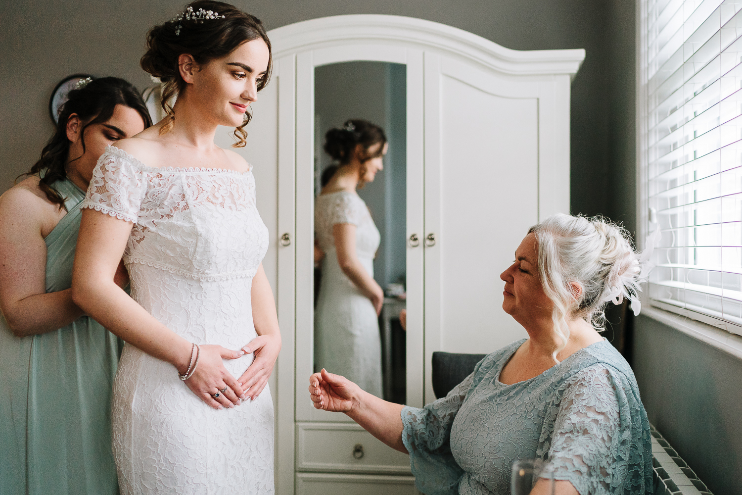 bride getting into her dress before marrying at the Barbour institute