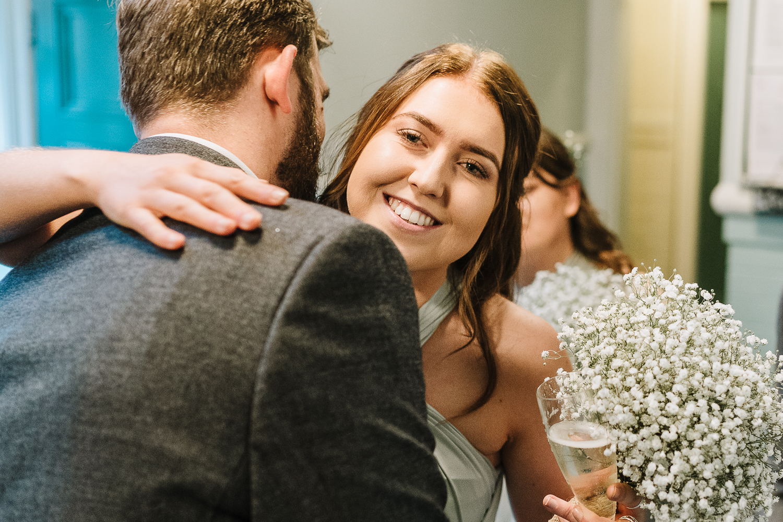Bridesmaid hugging the groom