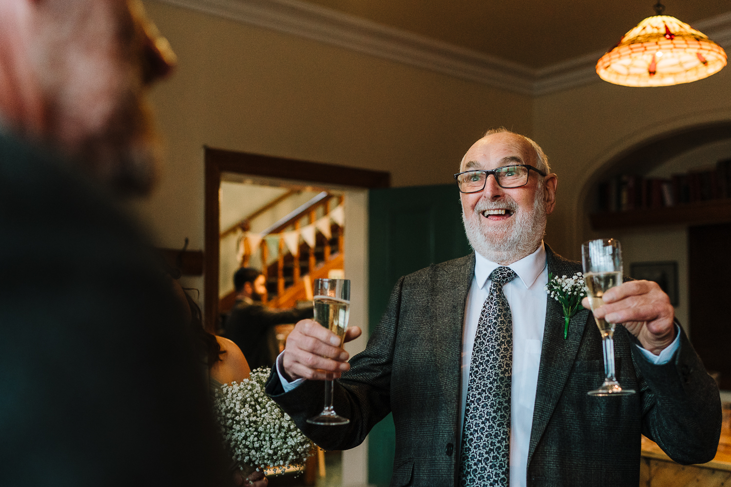 Brides grandad holding two drinks