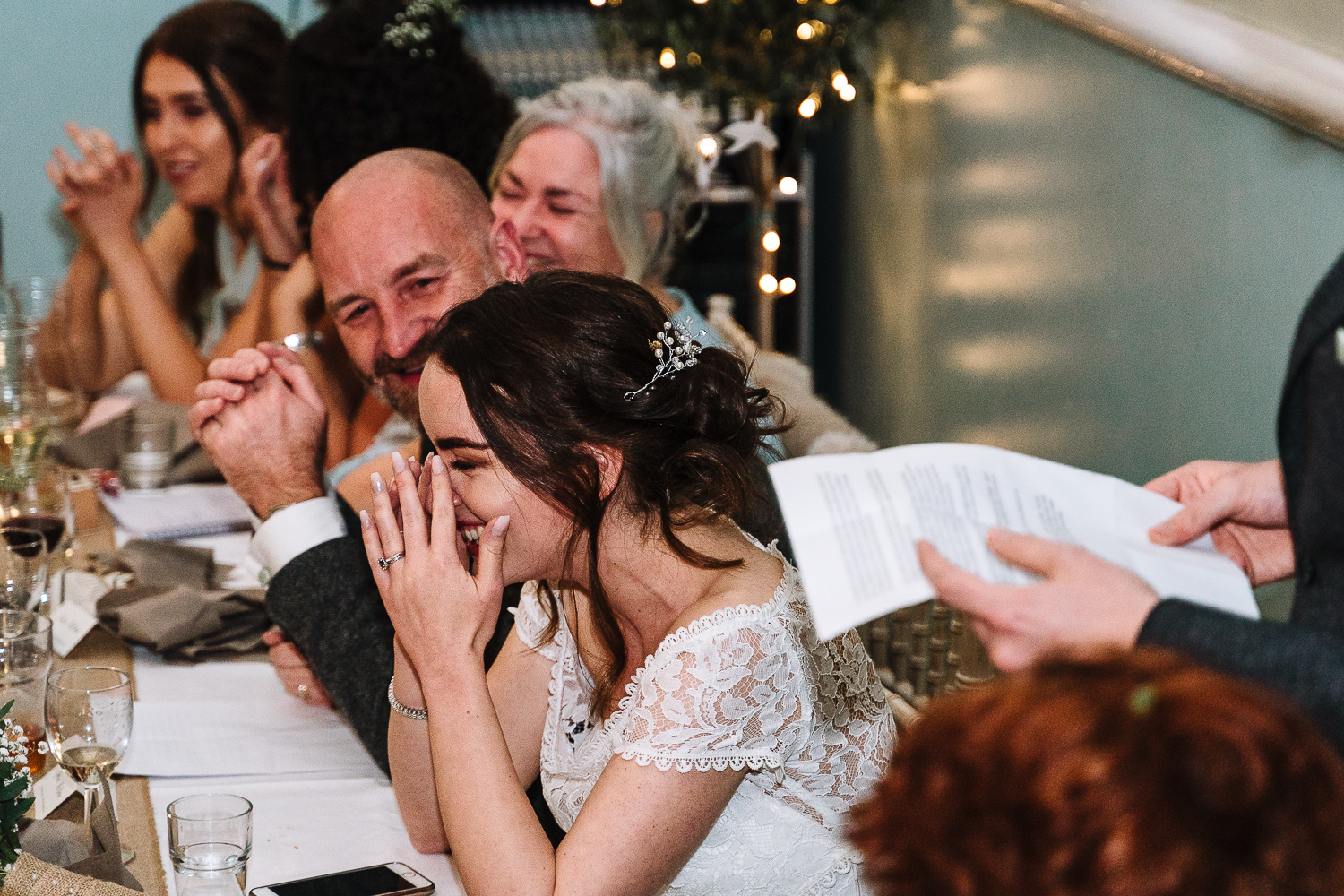Bride laughing during grooms speech
