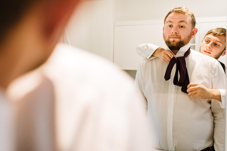 best man doing his tie