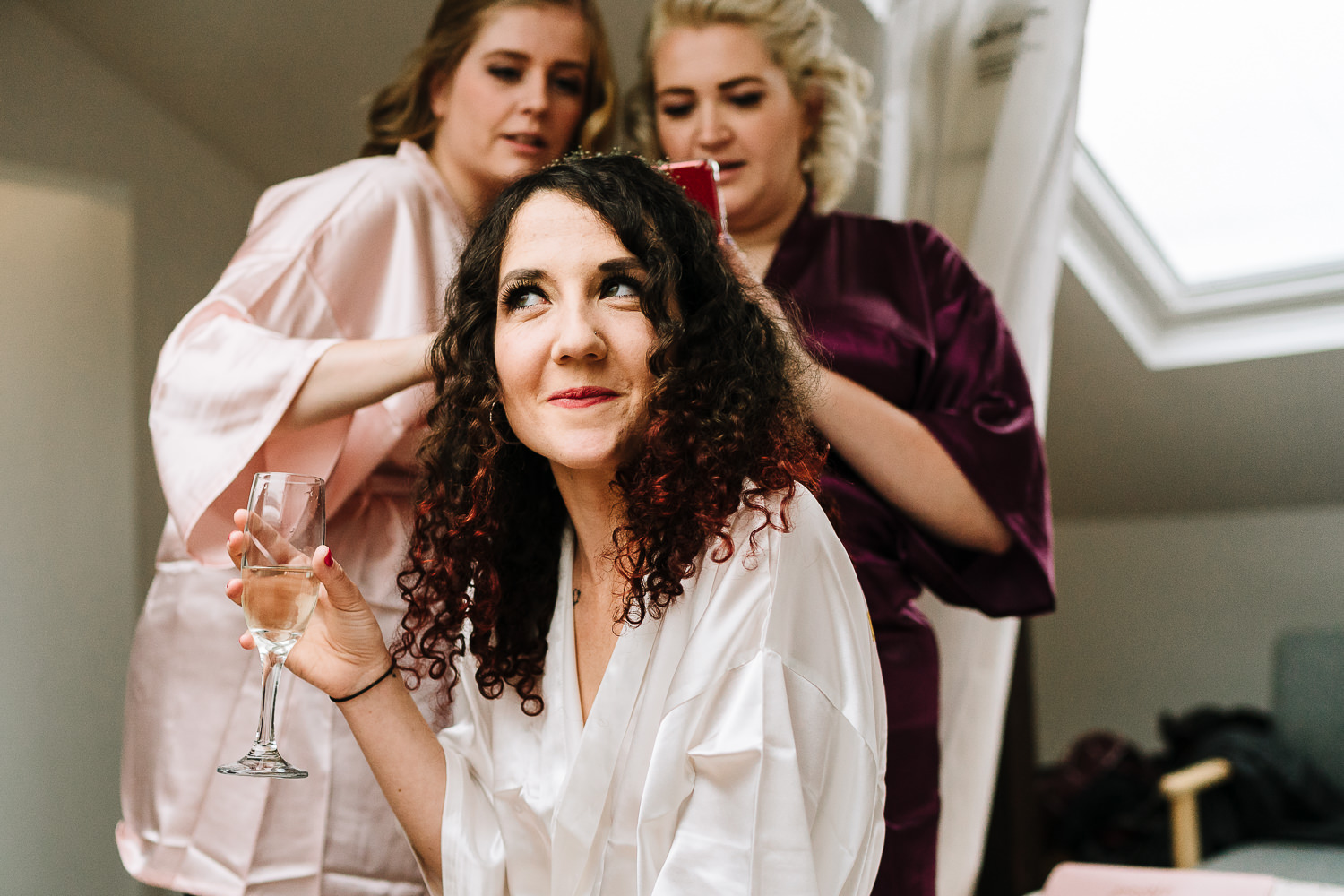 bride doing her hair and bridesmaids taking photos before going to Ashton Memorial