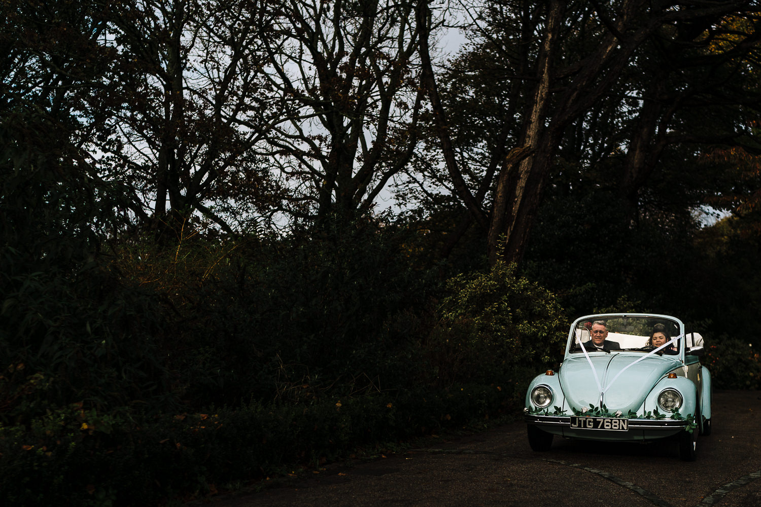 Bride and her dad being driven in a vw beetle