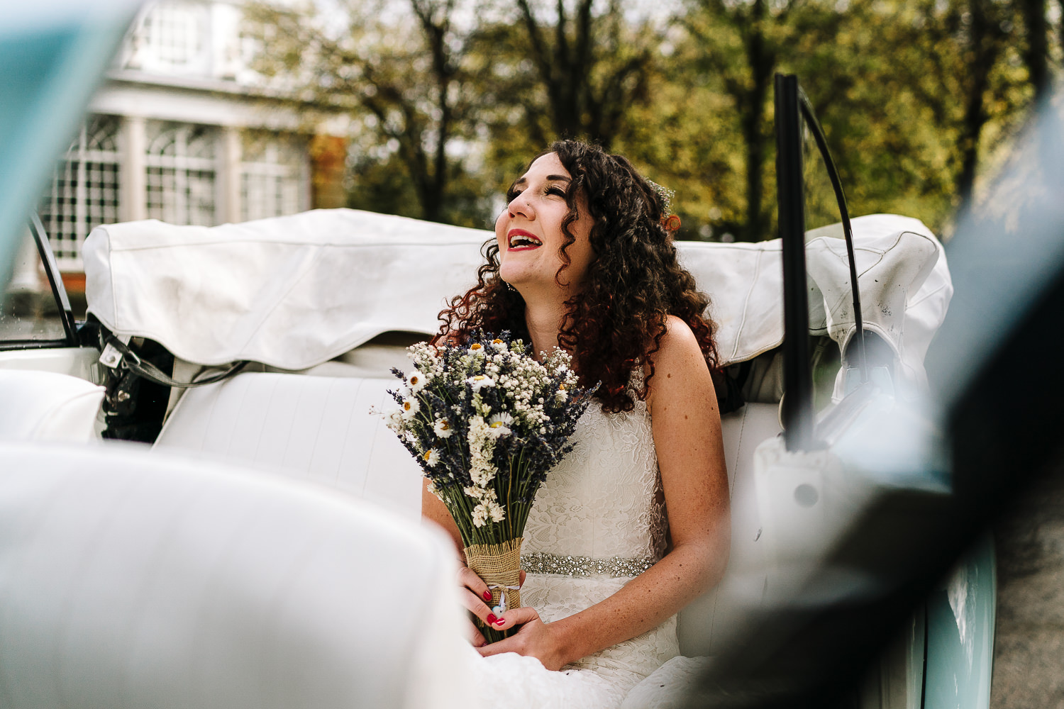 bride smiling in the car before getting married