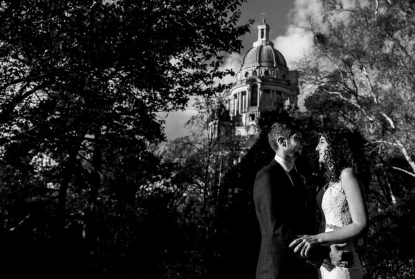 Bride and groom hugging with Ashton Memorial in the background