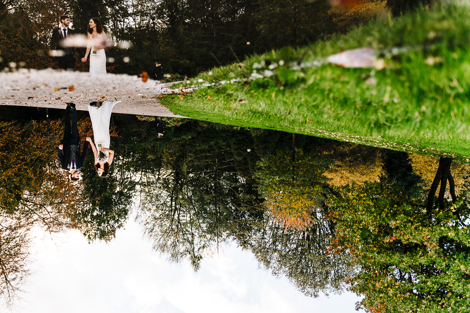 Bride and groom reflections in water