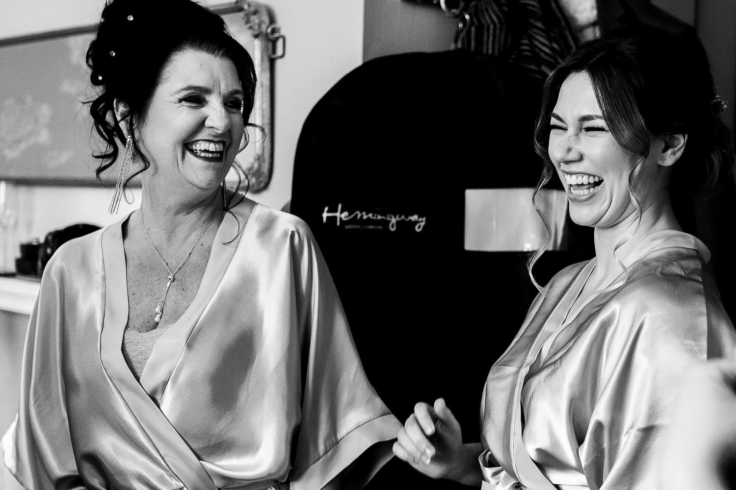 bridesmaid laughing with mother of the bride