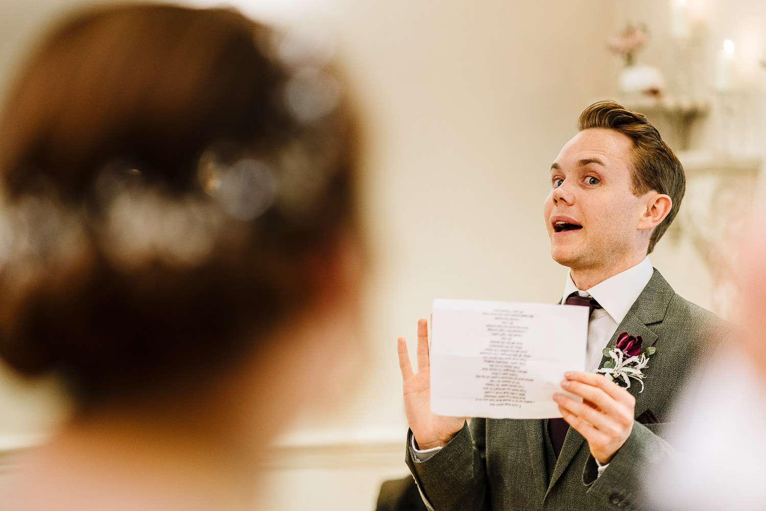 Groomsman laughing and holding his reading at Ashfield House