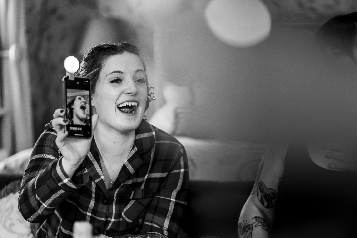Bridesmaid laughing at a photo on a phone