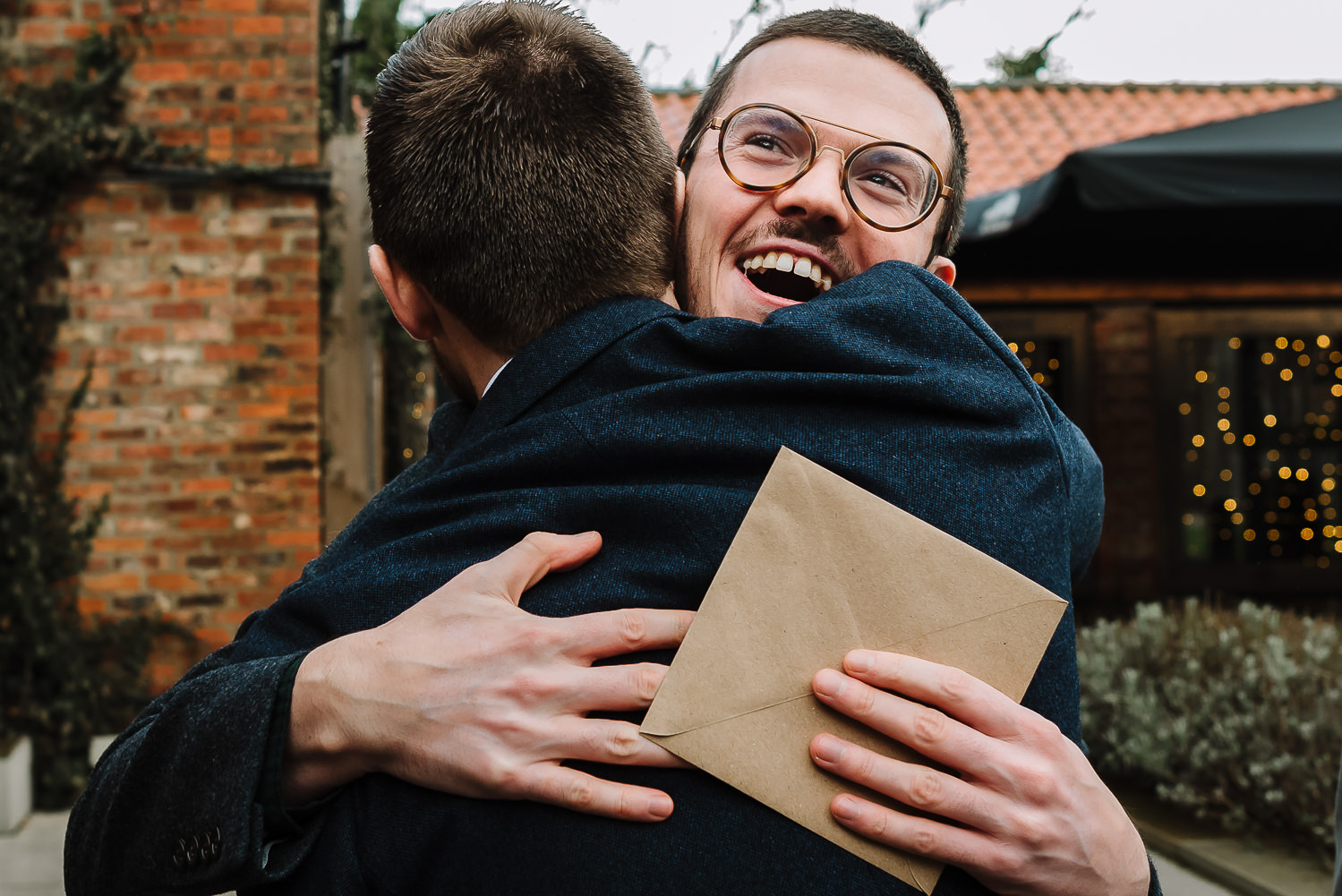 Groom hugging a male guest