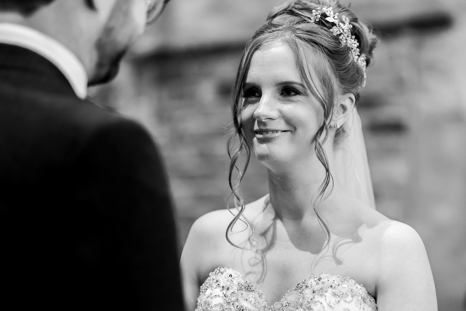 bride smiling at the groom during vows