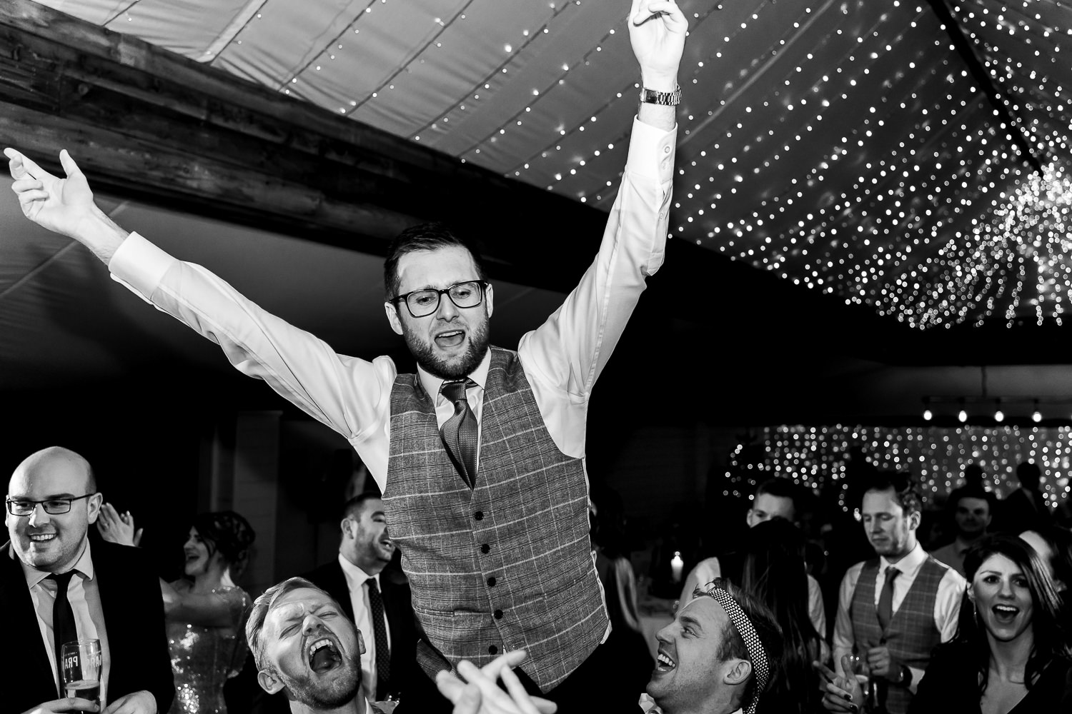 Groom being picked up on the dance floor